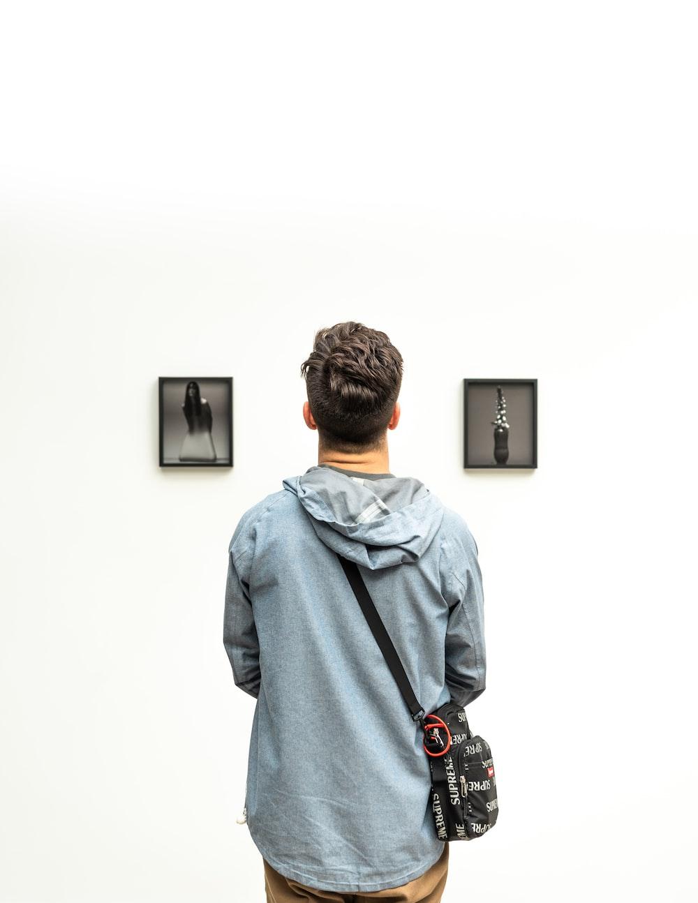man wearing hoodie looking at artworks