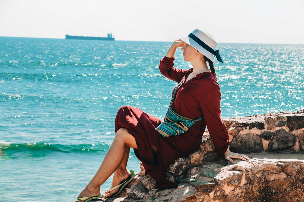 woman sitting on rock and putting right hand on her head viewing calm sea