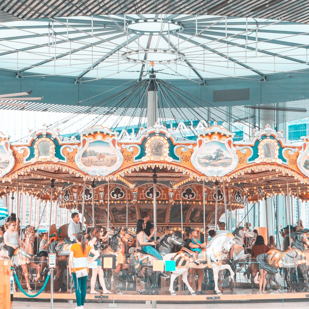 people riding merry go round during daytime