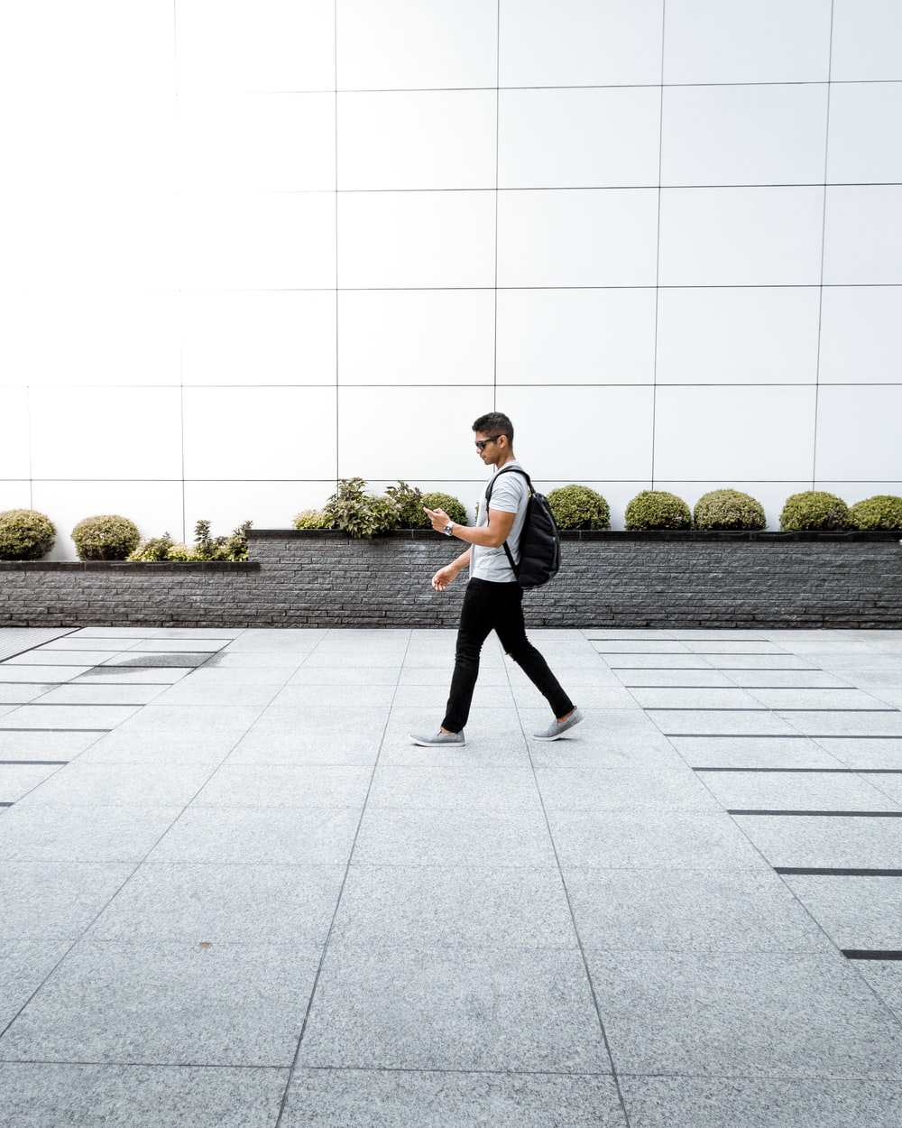 man with backpack using phone walking alone on pathway