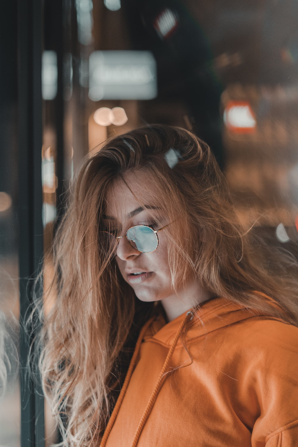 woman in orange pullover jacket and sunglasses