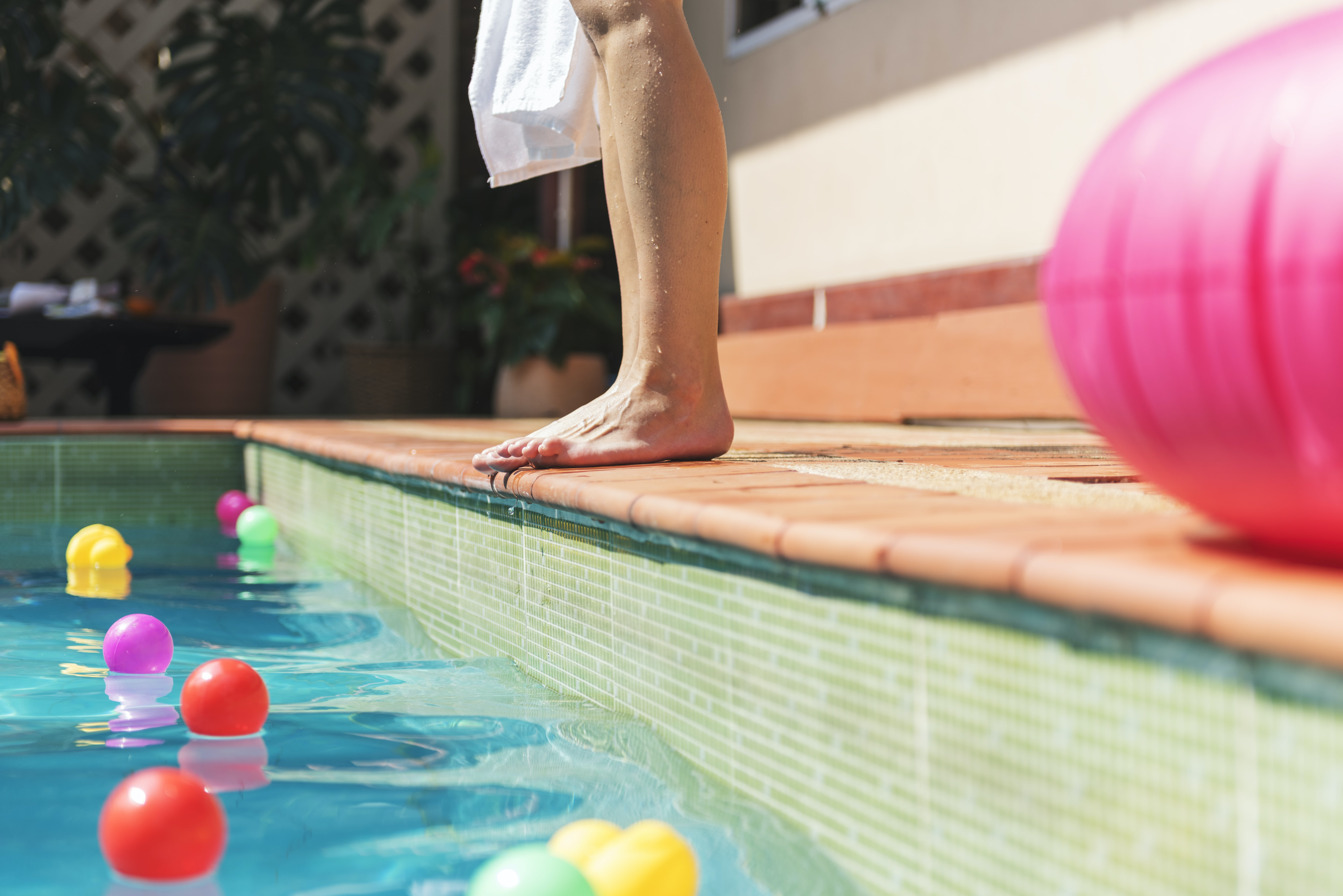 person standing near pool near pink inflatable ball during daytime