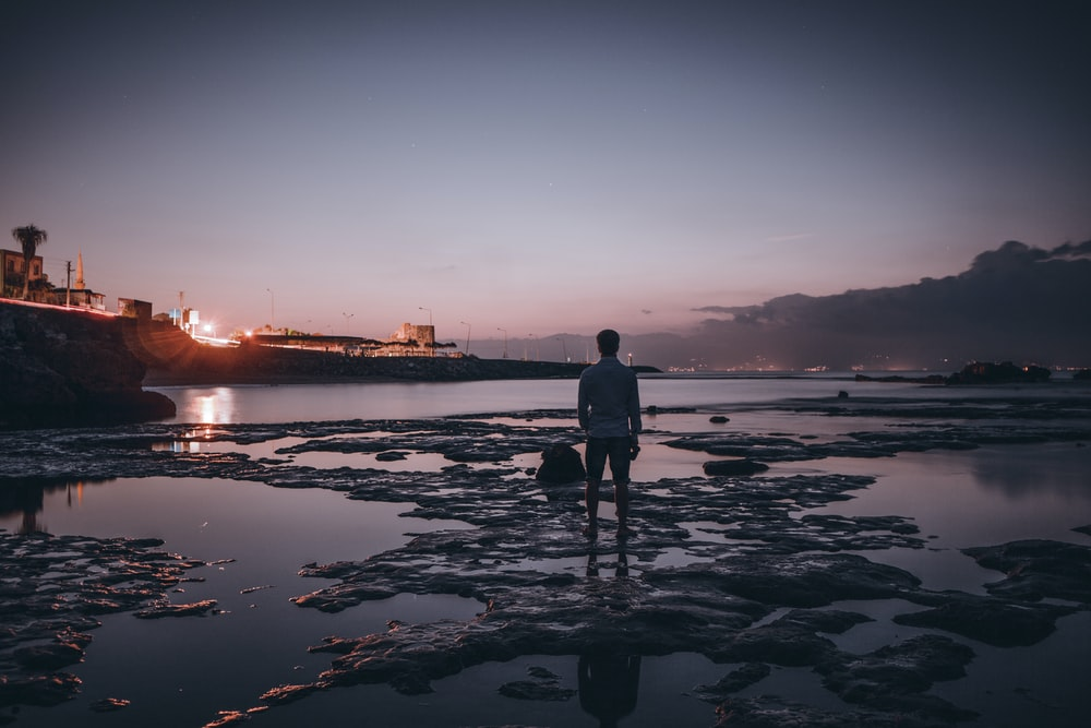 man standing on middle of beach in low tide