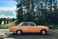 classic orange Mercedes-Benz sedan running on road during daytime