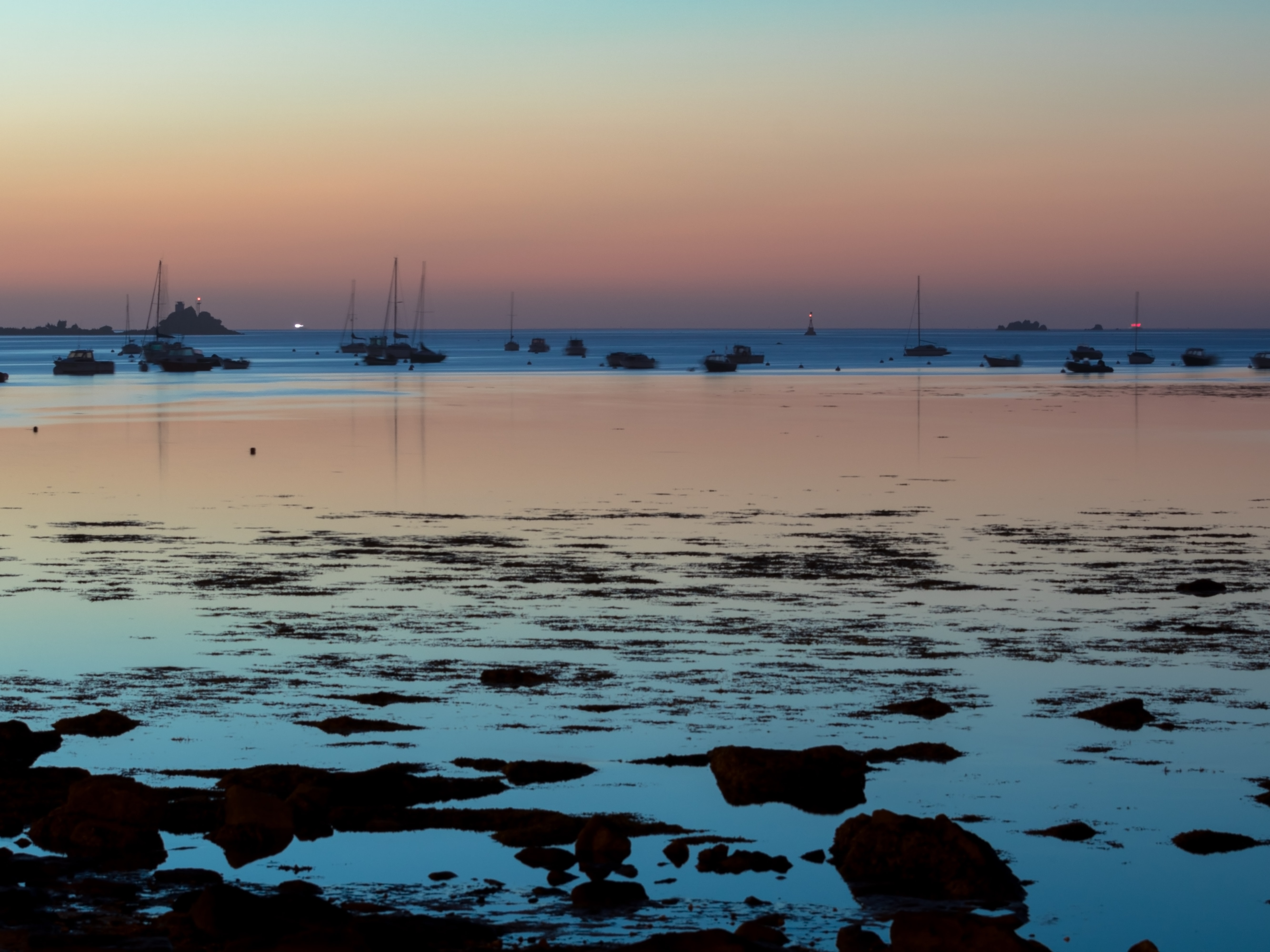 boats on seashore during golden hour