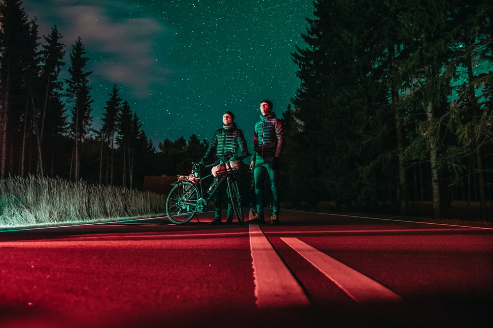 two men standing at center of road beside bicycle
