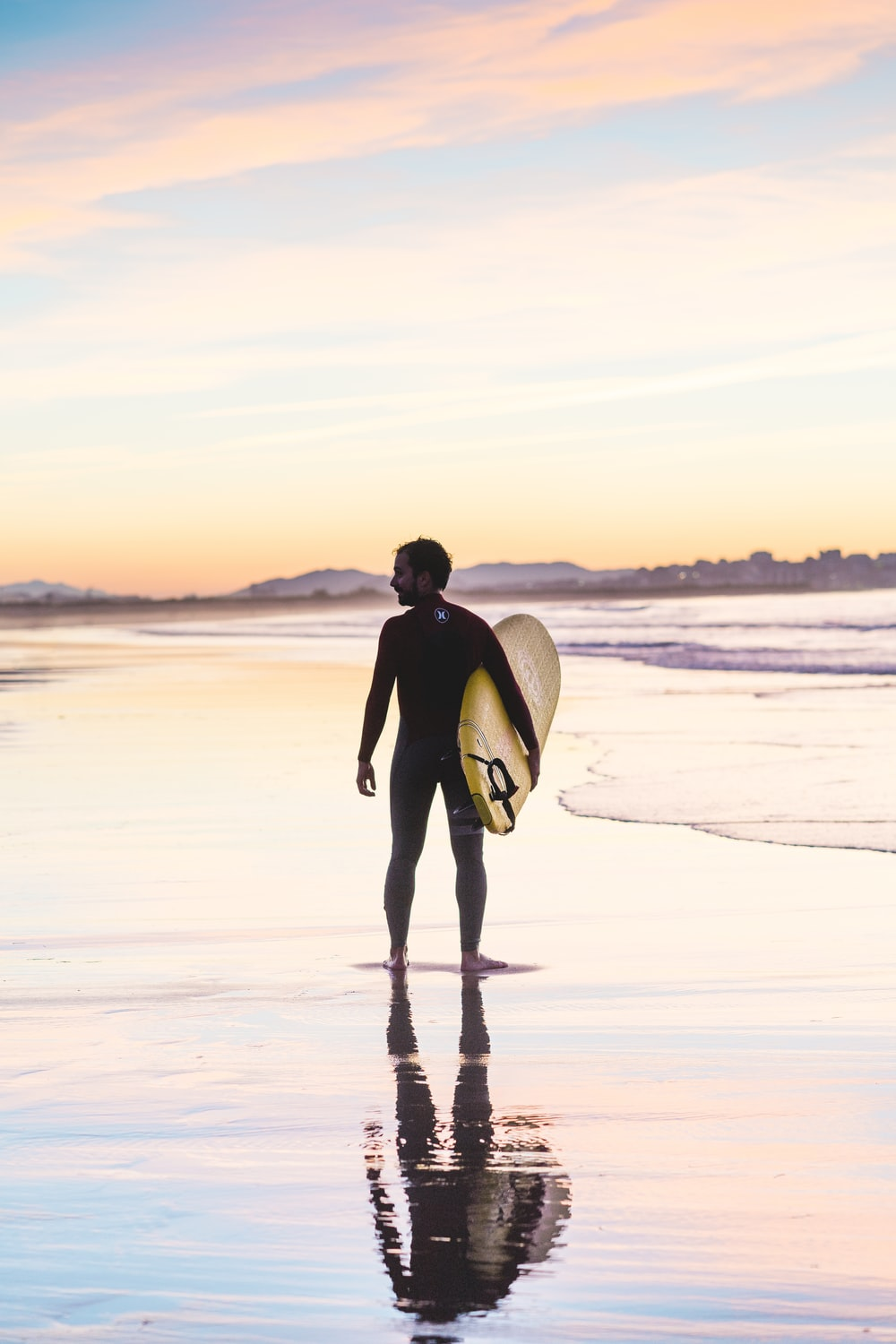 man holding surfboard standing on shore