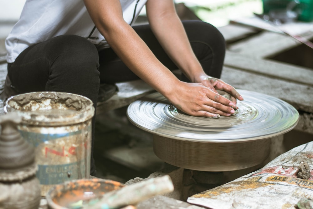 person sitting and molding with clay