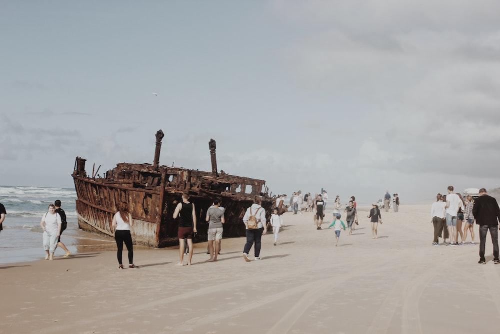 people walking besides brown ship
