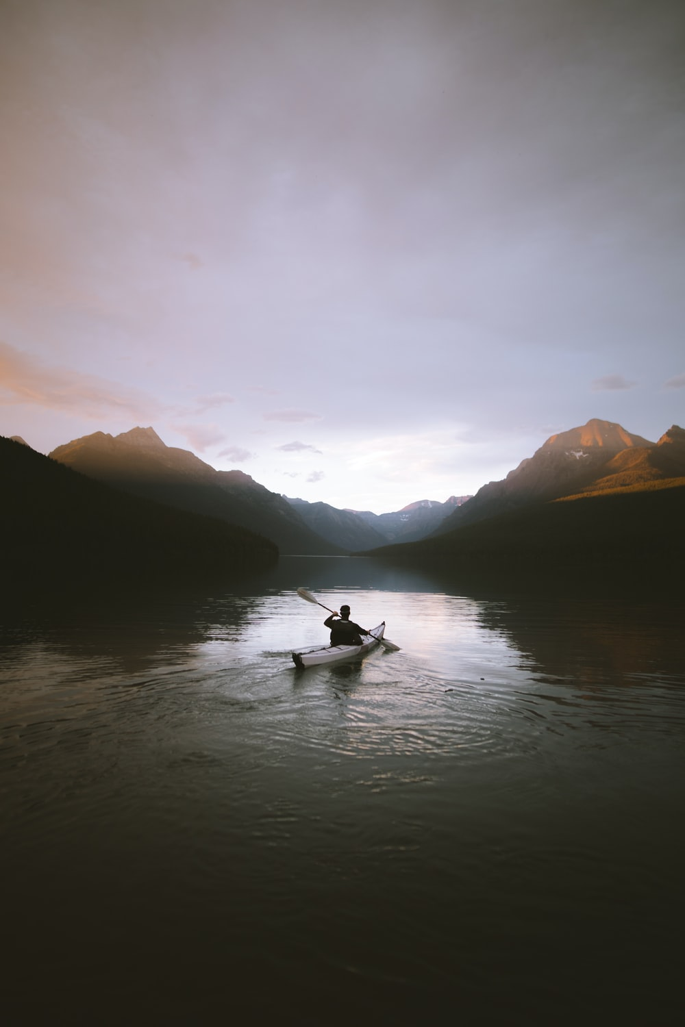 man paddling on boat on body of water