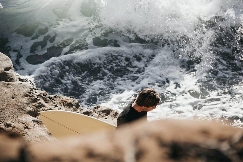 man holding surfboard beside sea