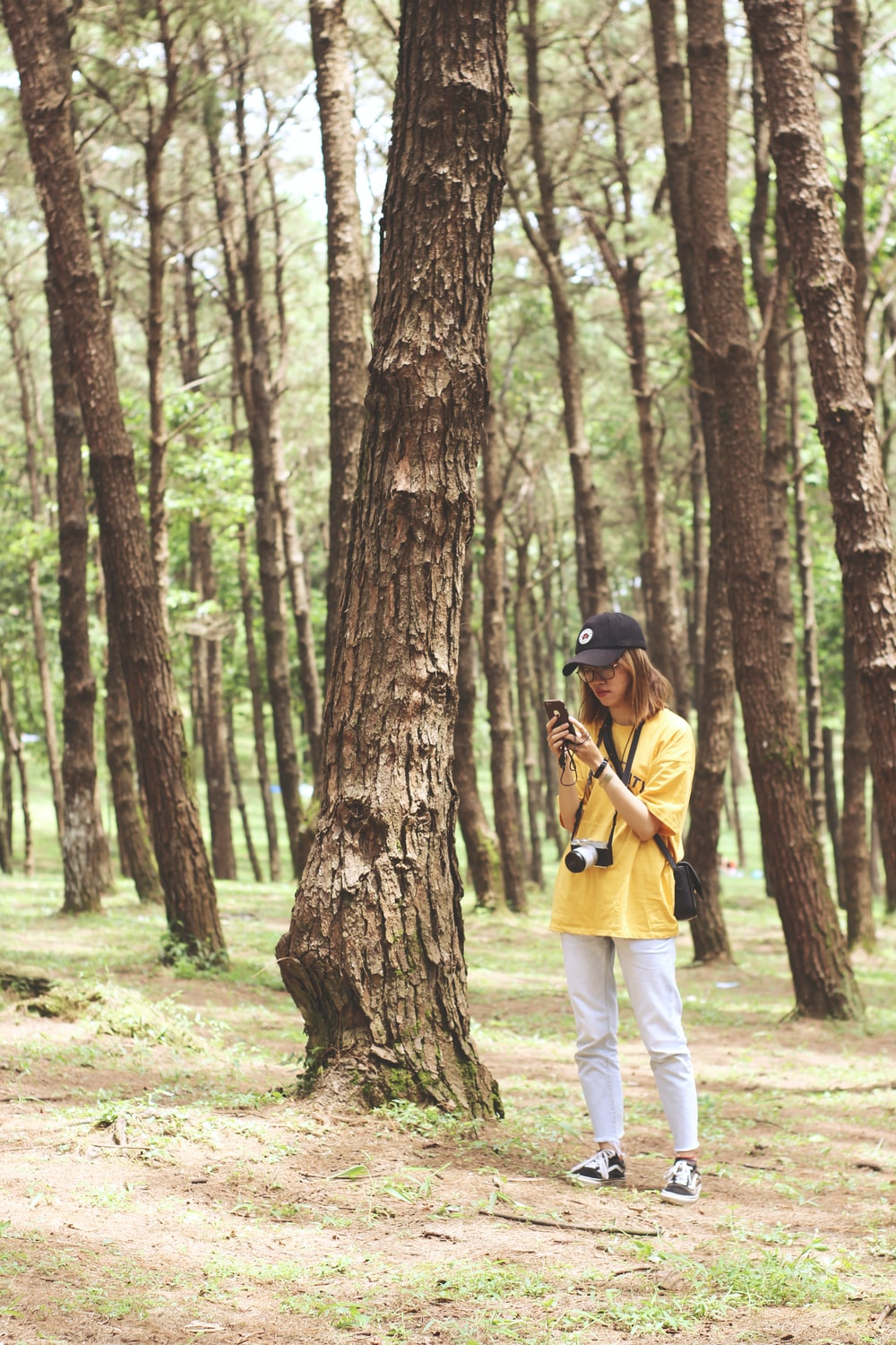 woman standing while holding smartphone beside tree during daytime