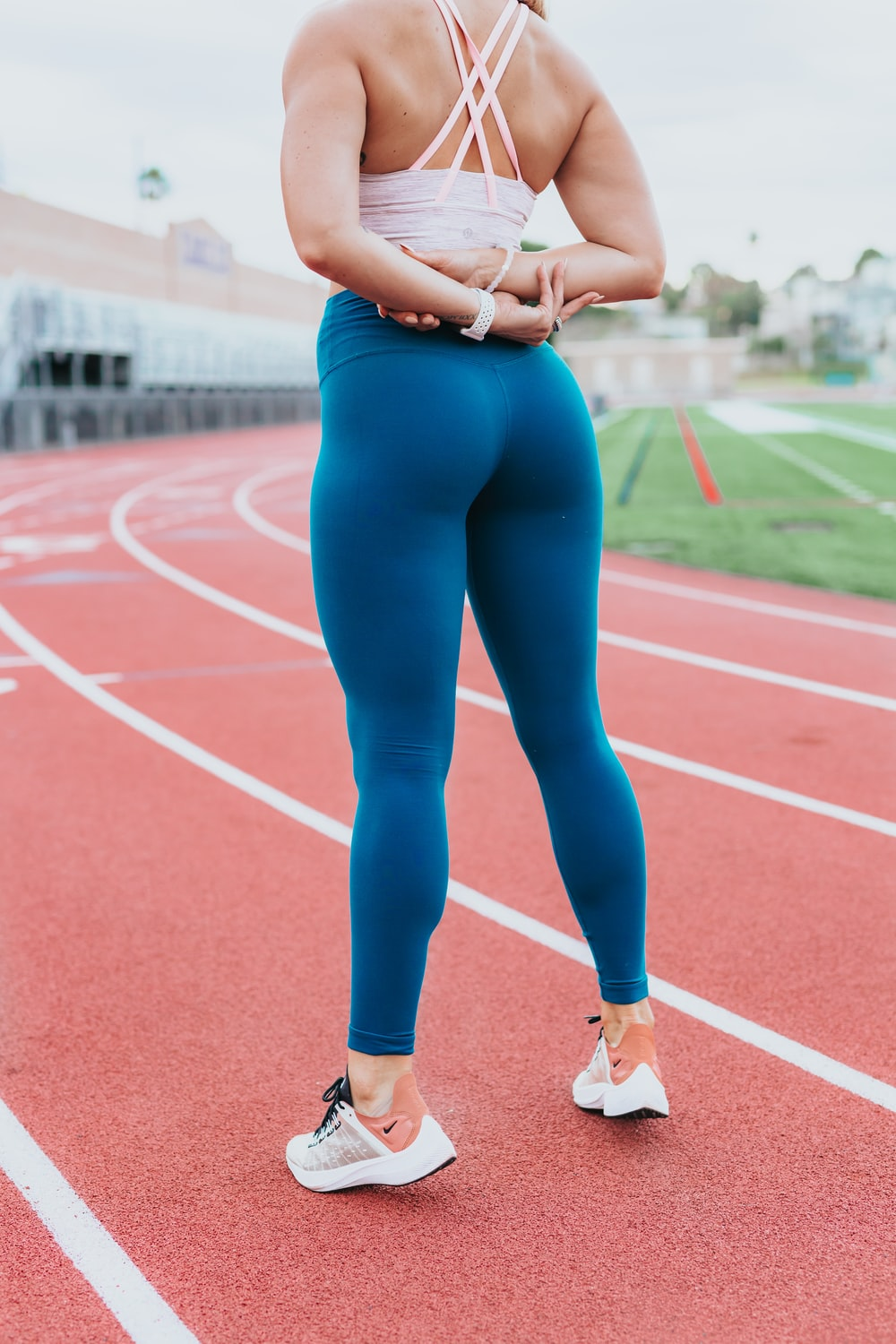 woman wearing blue pants standing on track during daytime