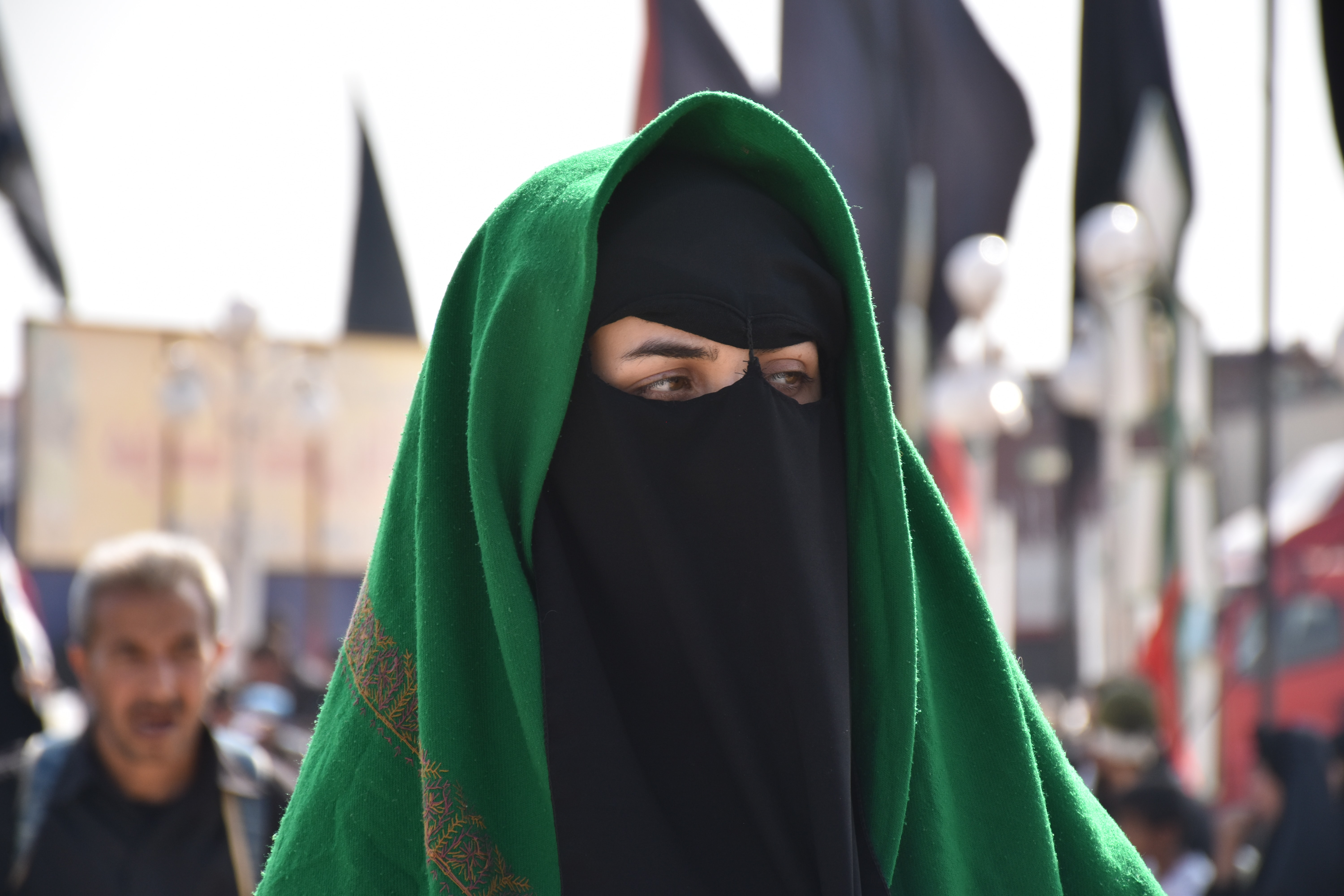tilt-shift lens photography of a woman wearing black and green mask