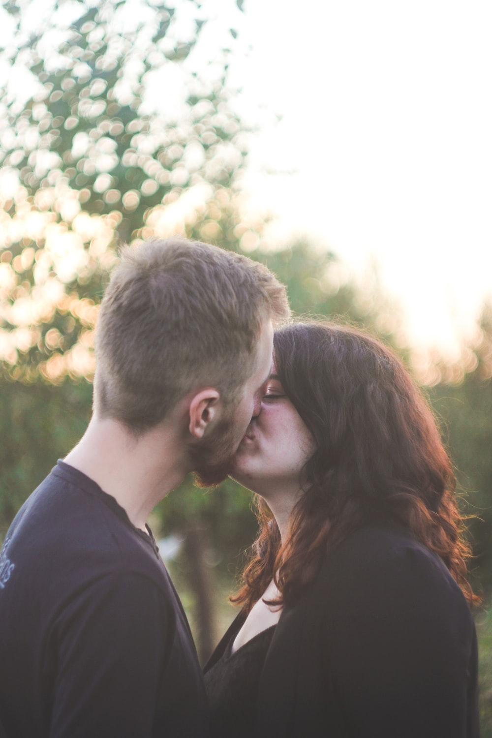 man and woman kissing during daytime