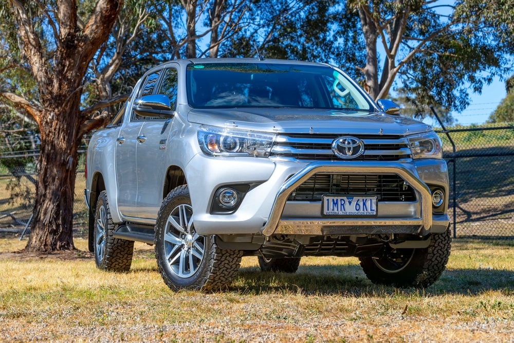 silver Toyota Hilux crew cab pickup truck parking near trees