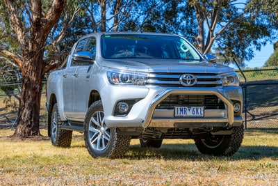 silver toyota hilux crew cab pickup truck parking near trees toyota zoom background