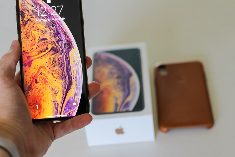 person holding space gray iPhone Xs Max