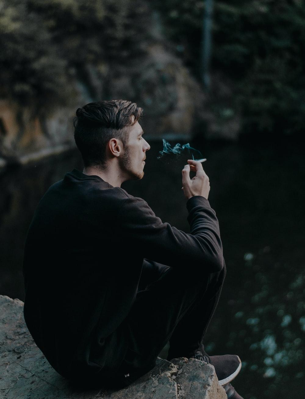 man sitting on cliff while smoking