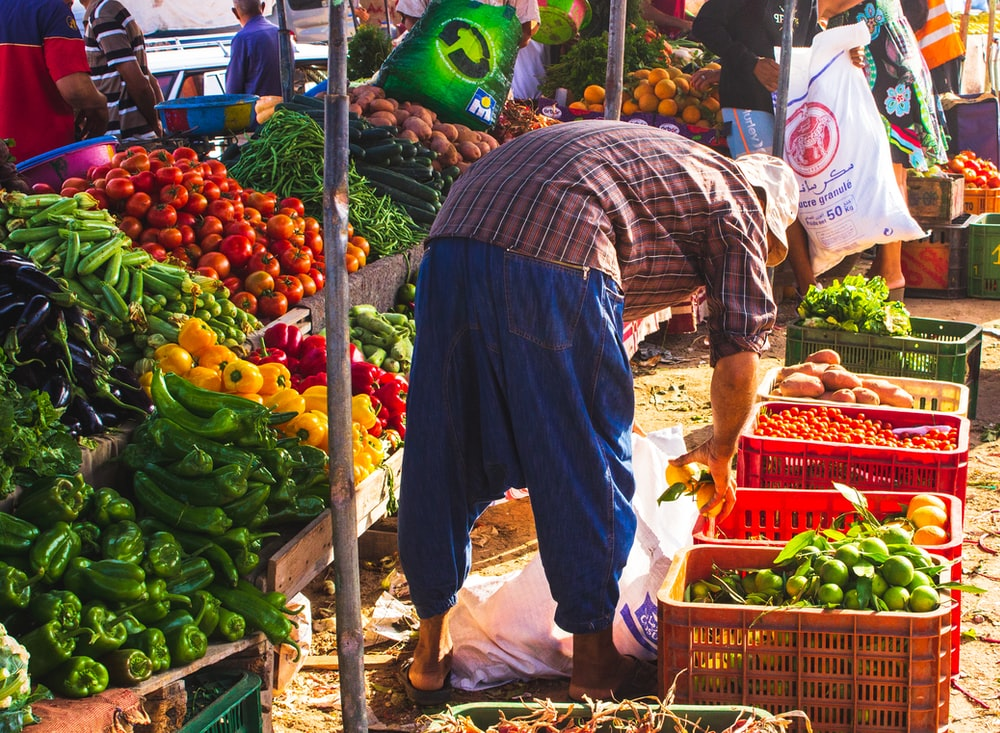 person surrounded by vegetables