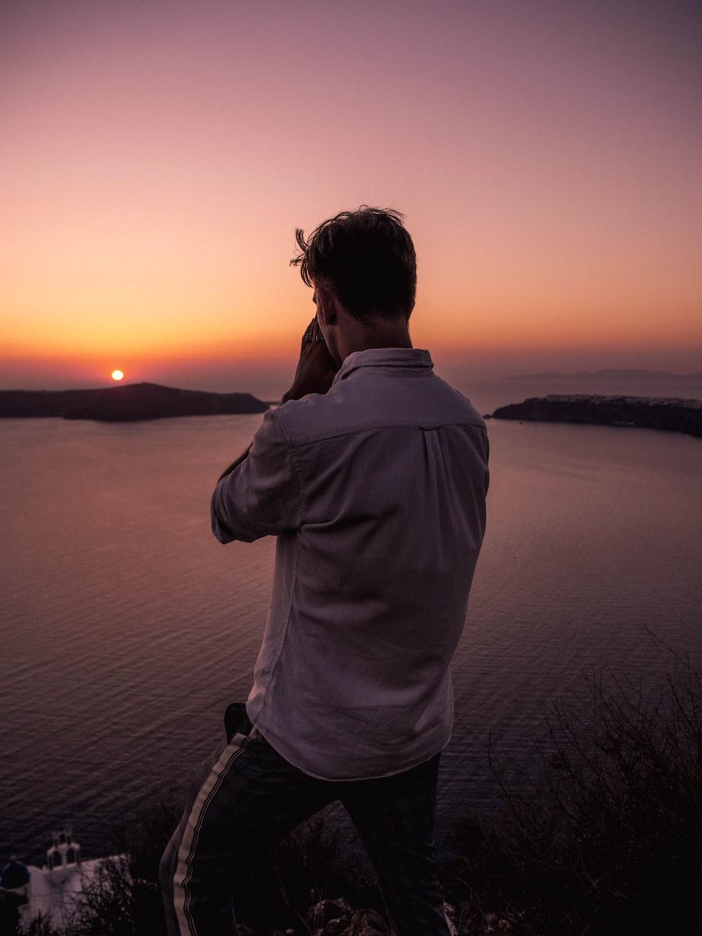 man wearing dress shirt standing on cliff during golden hour
