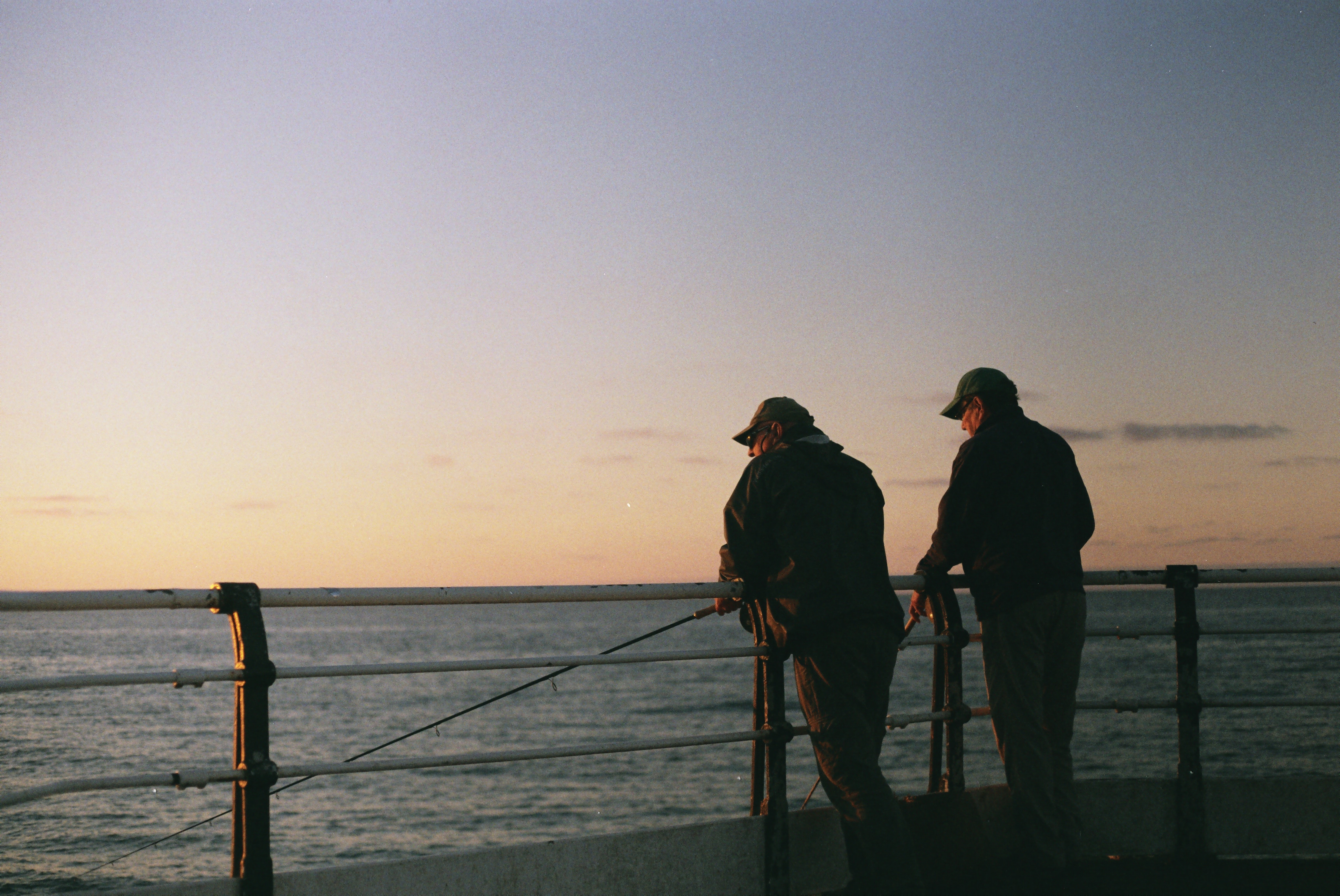 two men fishing by the railing