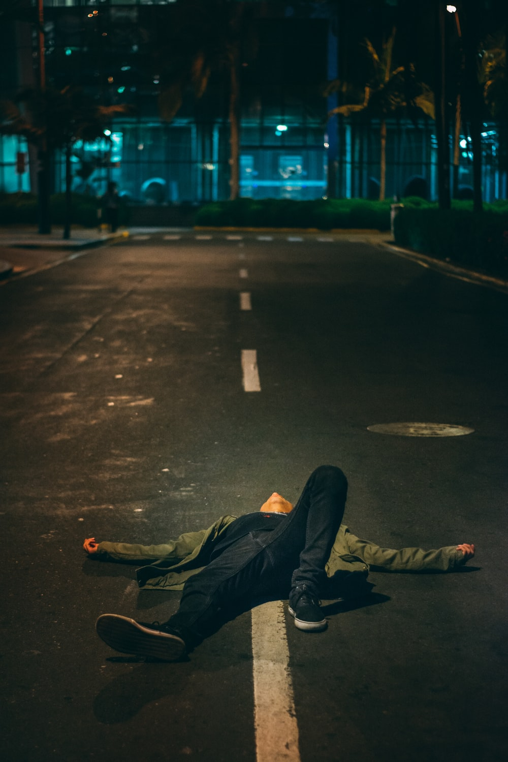 man laying down on road during nighttime