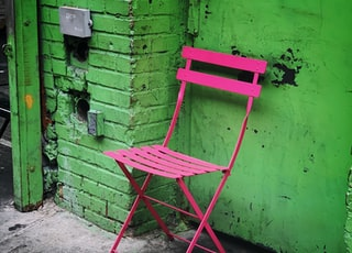 vacant pink armless chair near green wall
