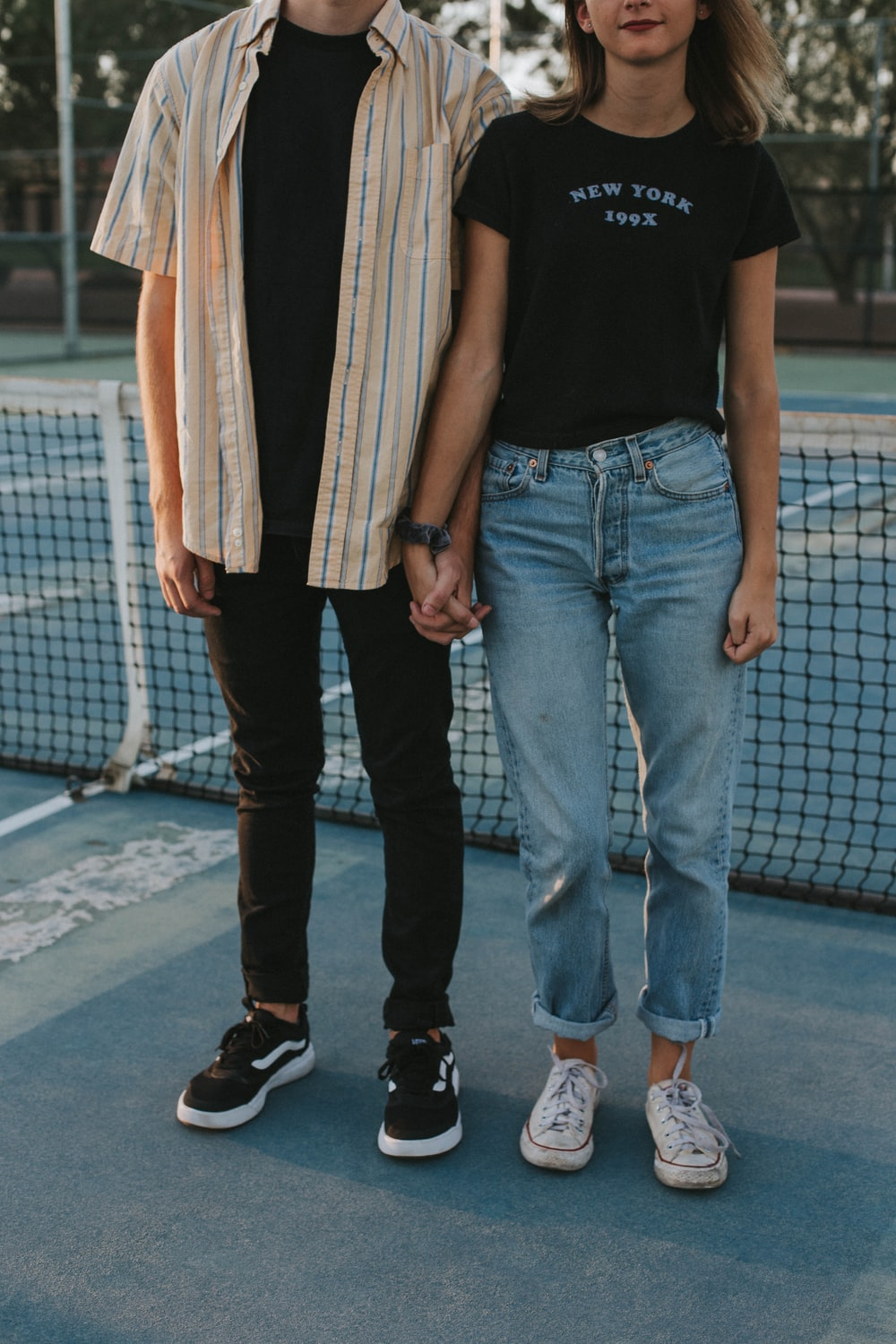 woman and man standing side by side while holding hands in tennis court