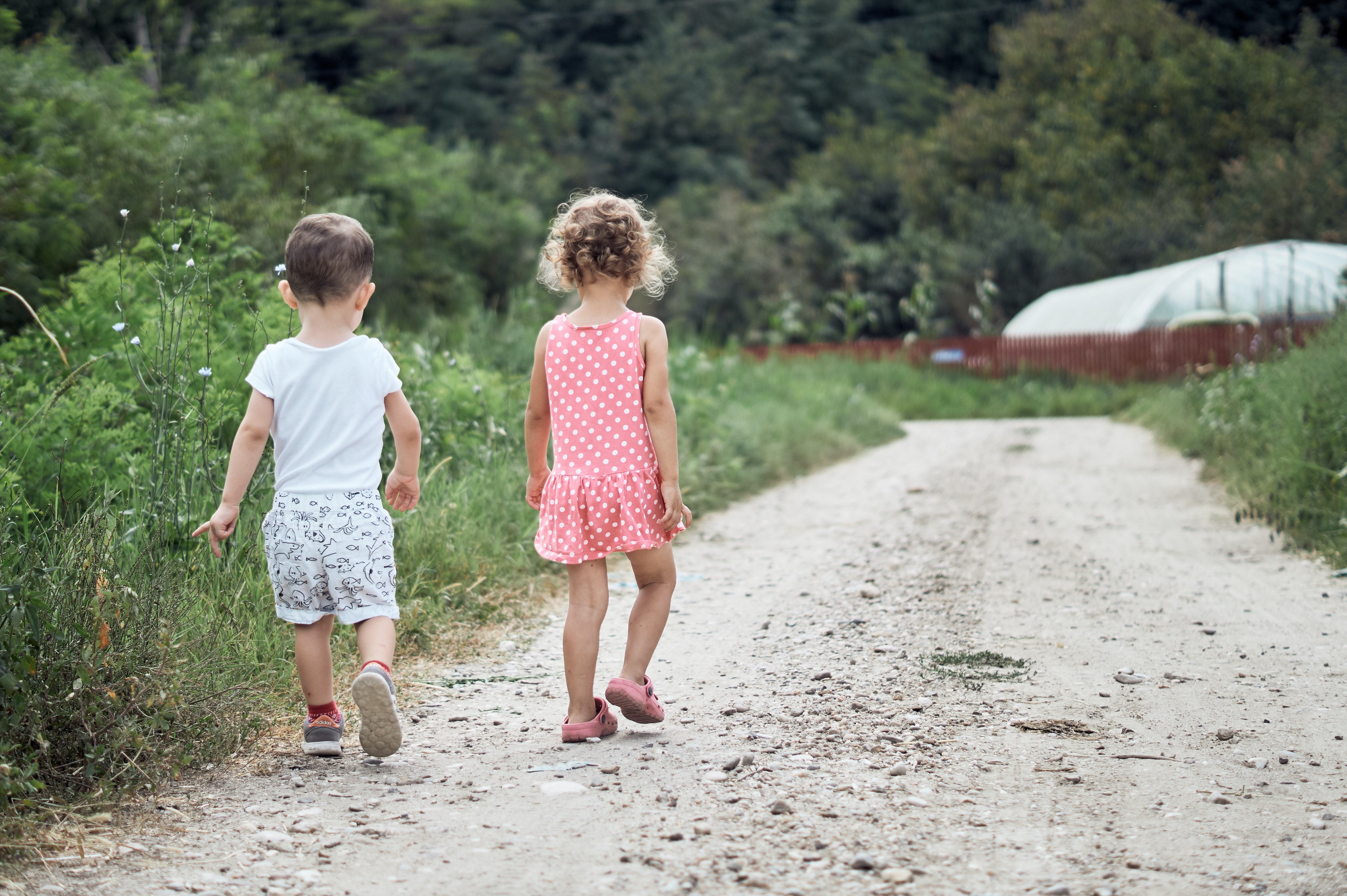 girl and boy walking on the side of the road