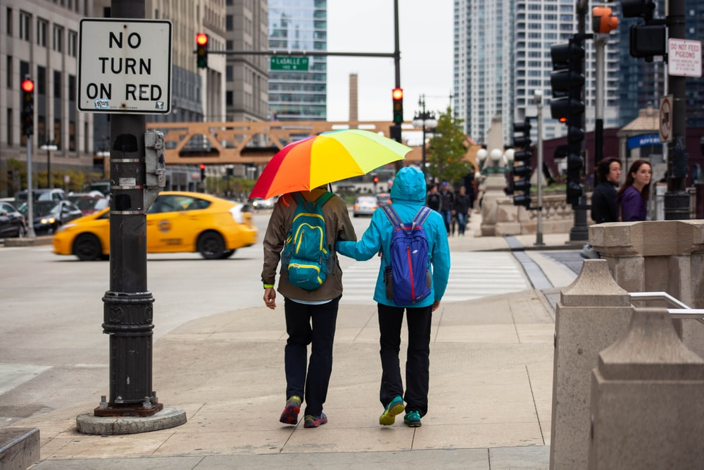 couple wearing jackets under colorful umbrella at the street