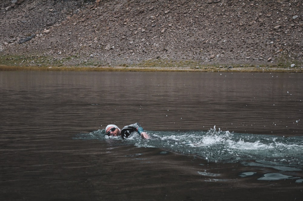 man swimming on body of water