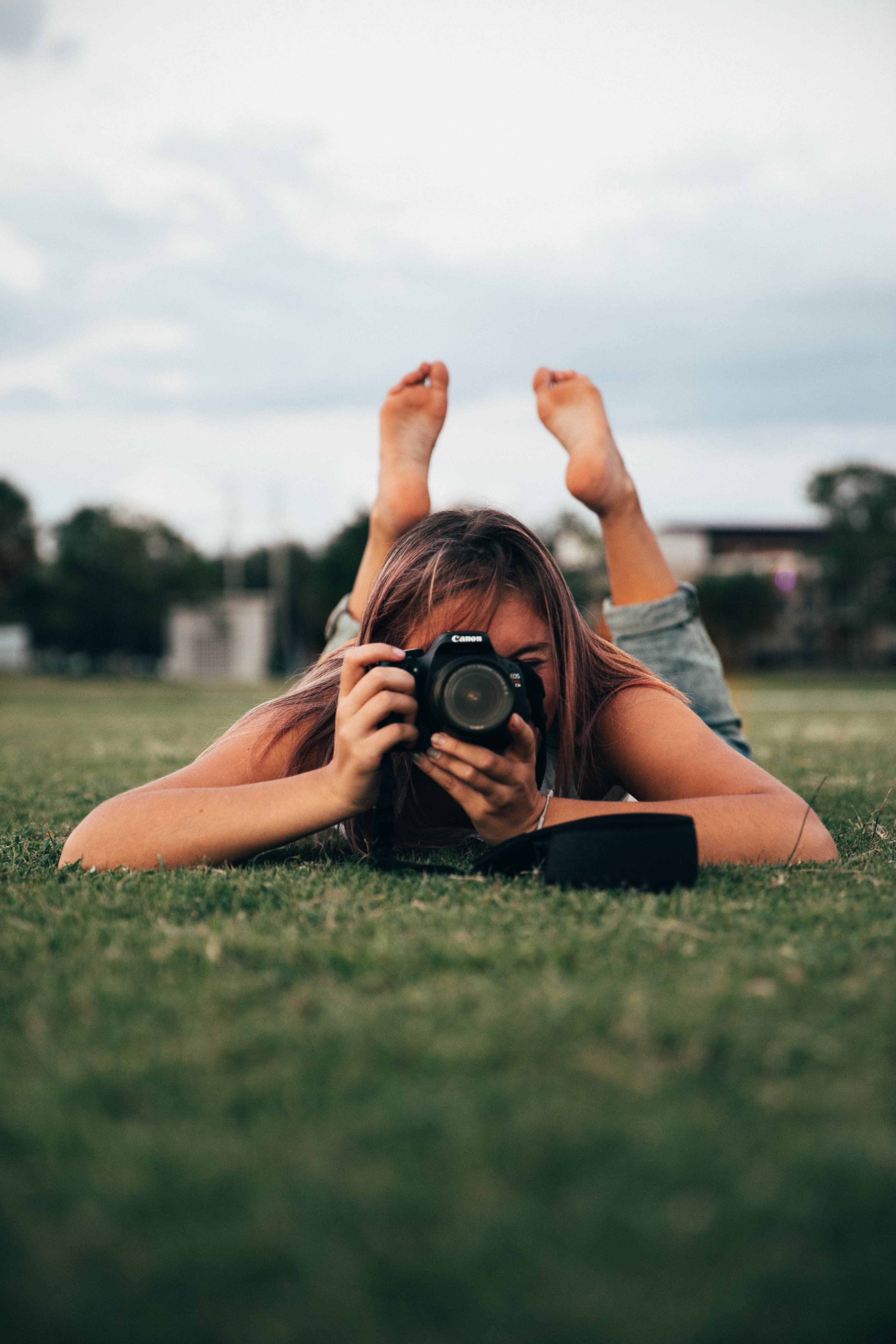 woman lying on grass while holding DSLR camera