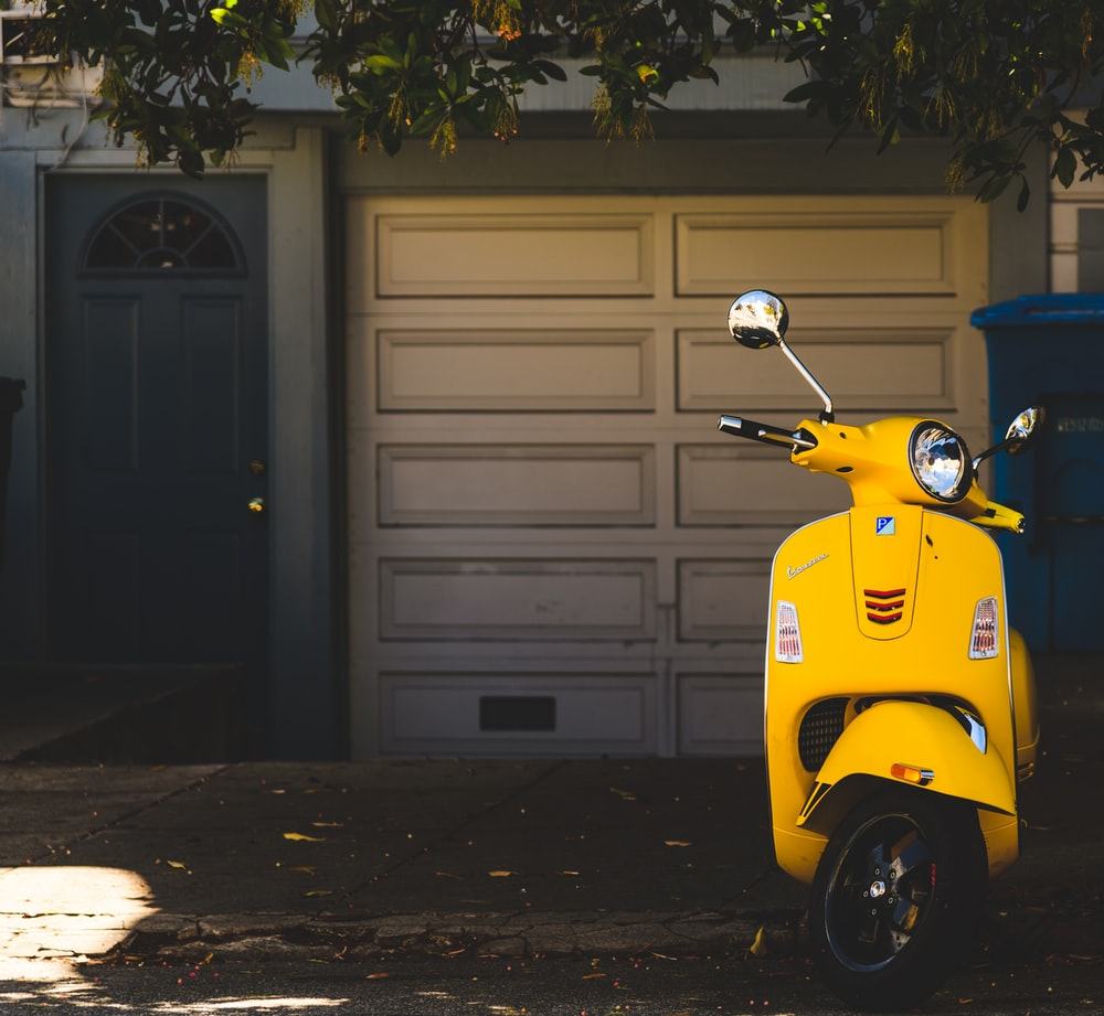 yellow motor scooter parked near white garage door
