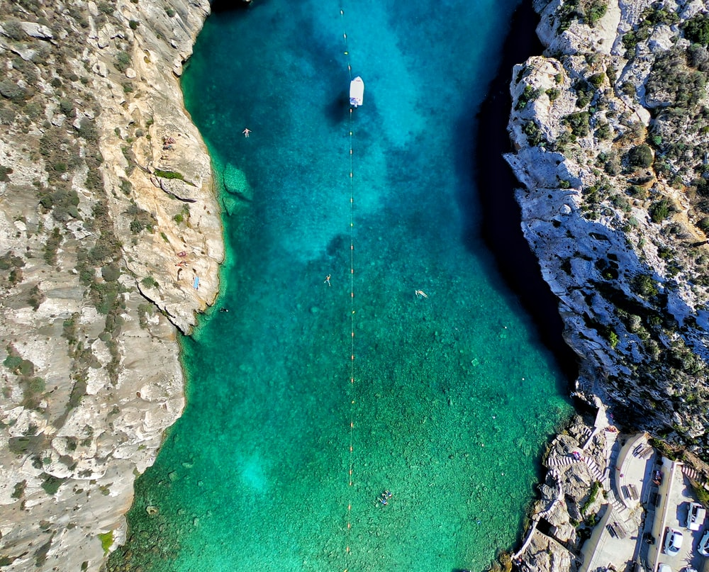 green body of water surrounded by rock formation aerial photography