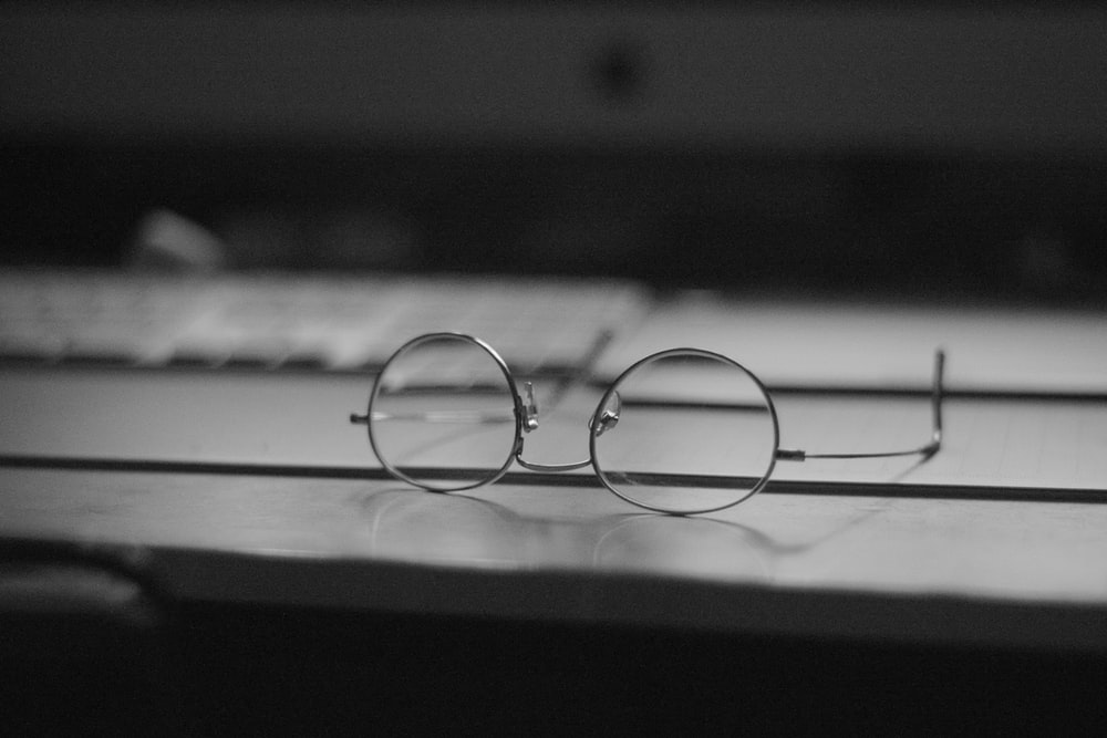 gray eyeglasses on top table