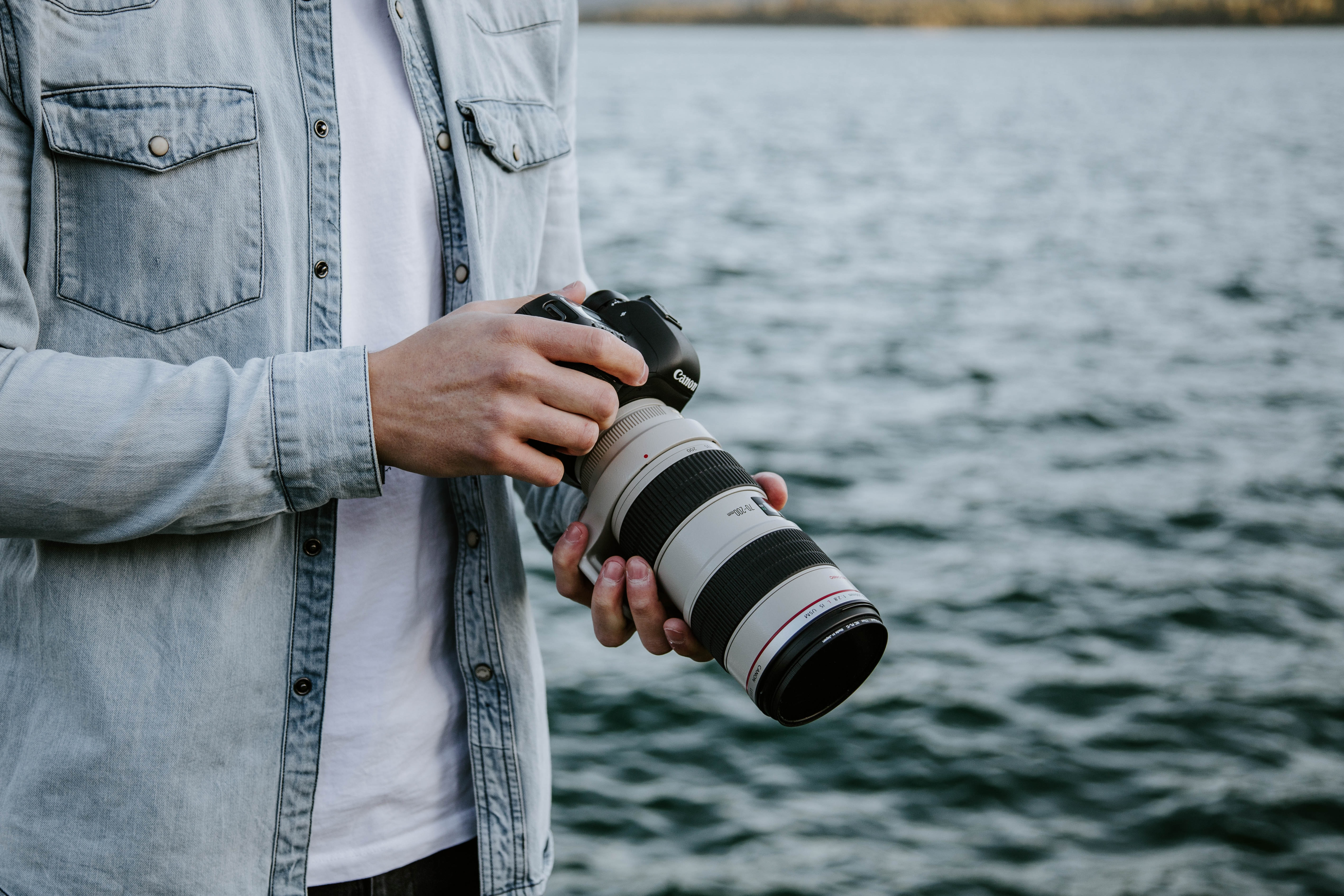 person holding white and black DSLR camera near body of water