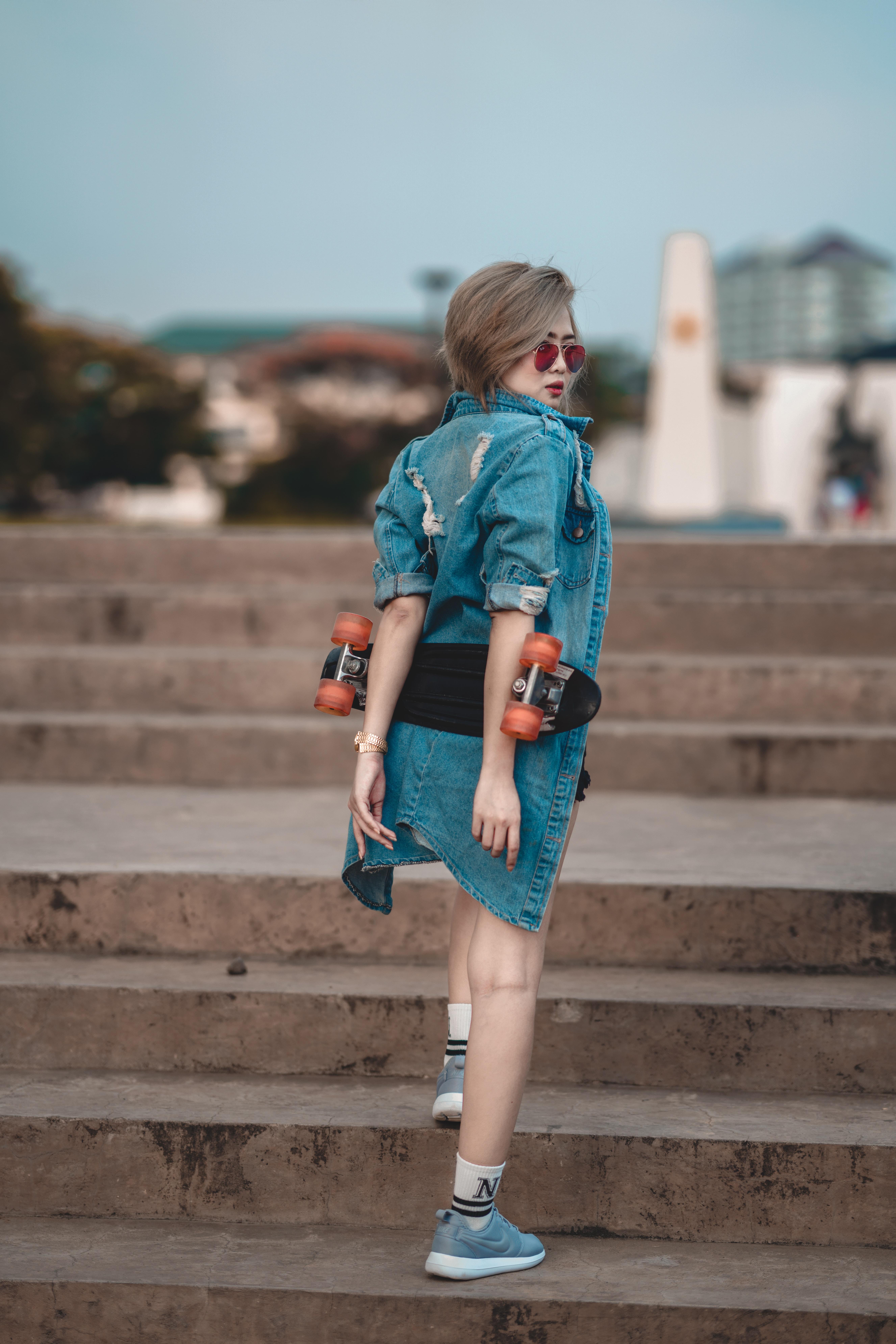 woman wearing blue denim jacket walking on stair at daytime