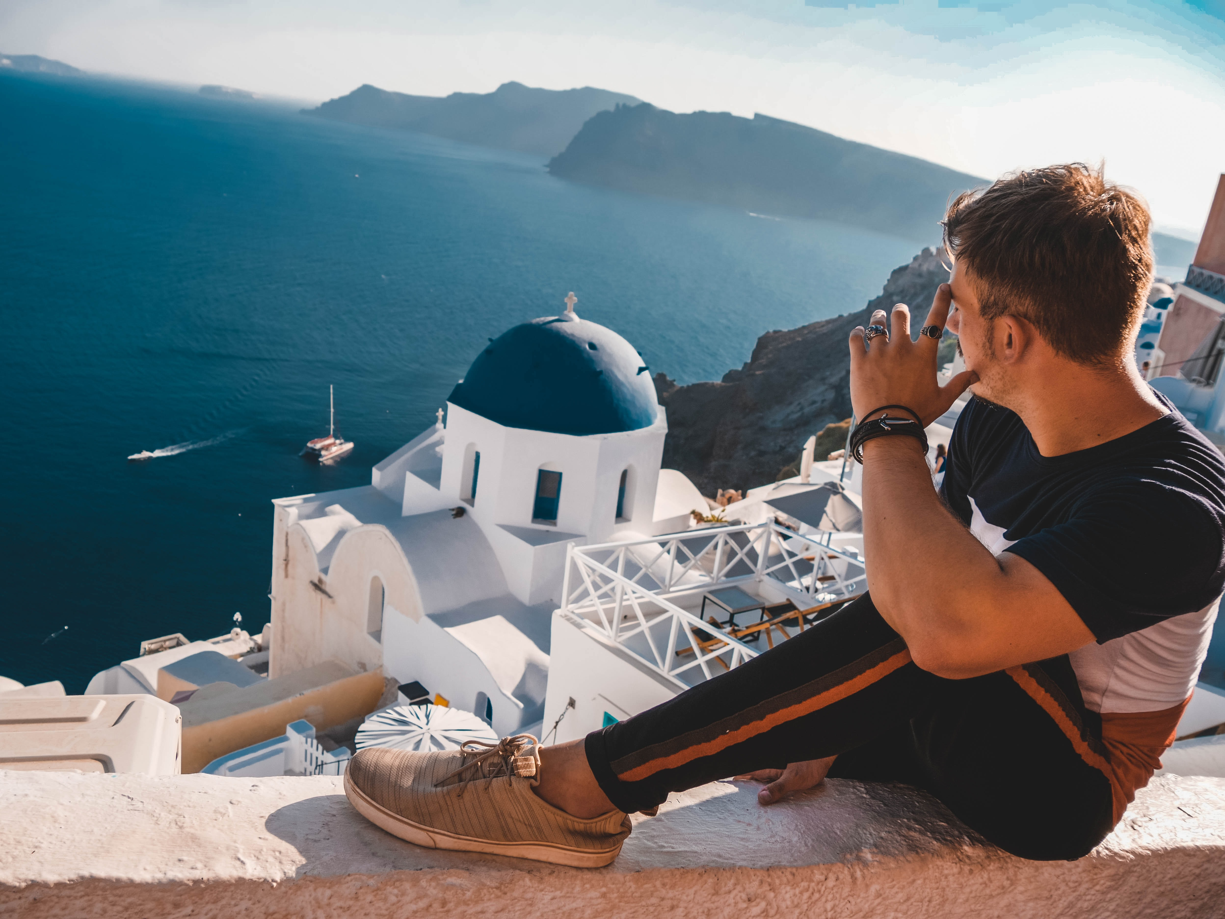 man sitting on concrete railing overlooking dome in Santorini at daytime