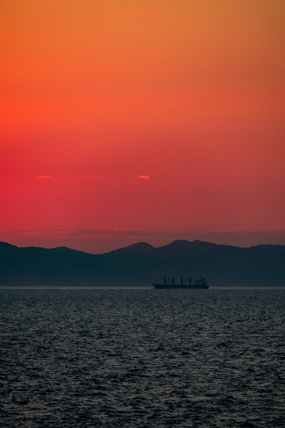 sillhoutte photography of ship in the sea during golden hour