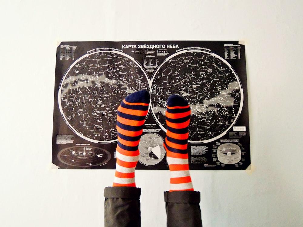 pair of orange-and-blue striped socks on black poster
