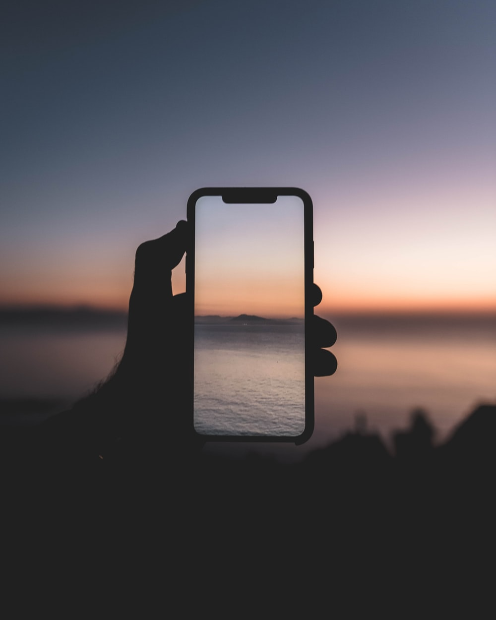 silhouette of person taking picture of body of water