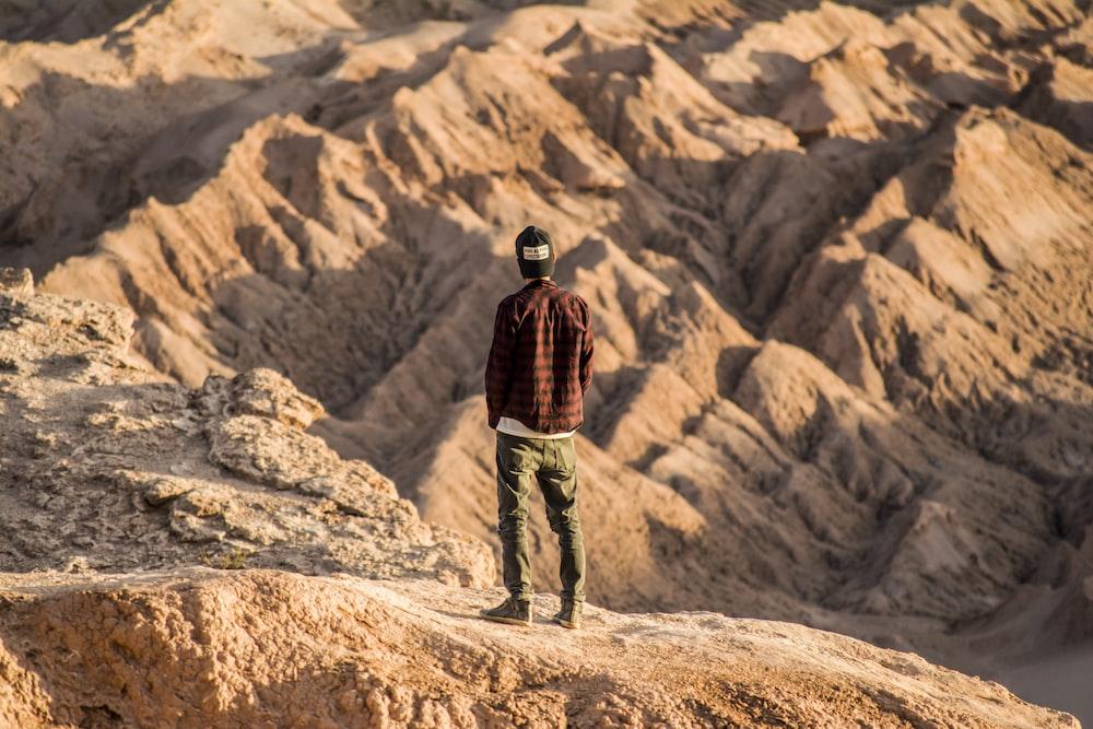 man standing on mountain range during daytime