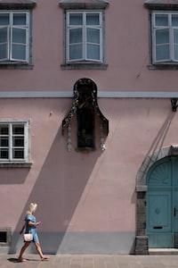 woman walking on the street beside pink concrete building