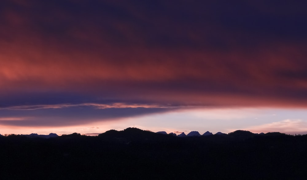 silhouette photograph of mountain ranges during golden hour