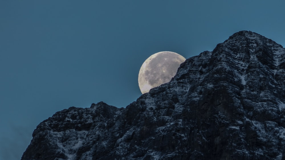 moon behind rock mountain