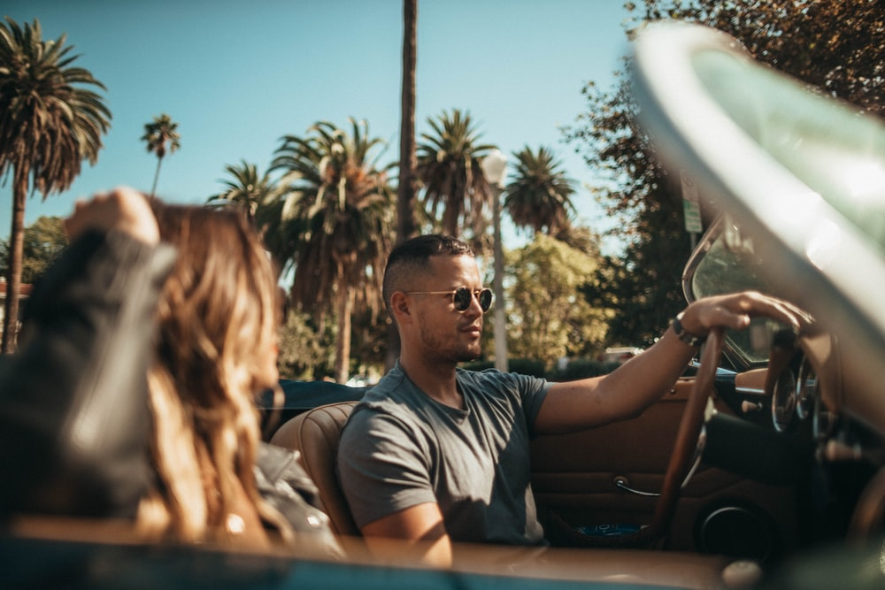 man driving convertible beside woman