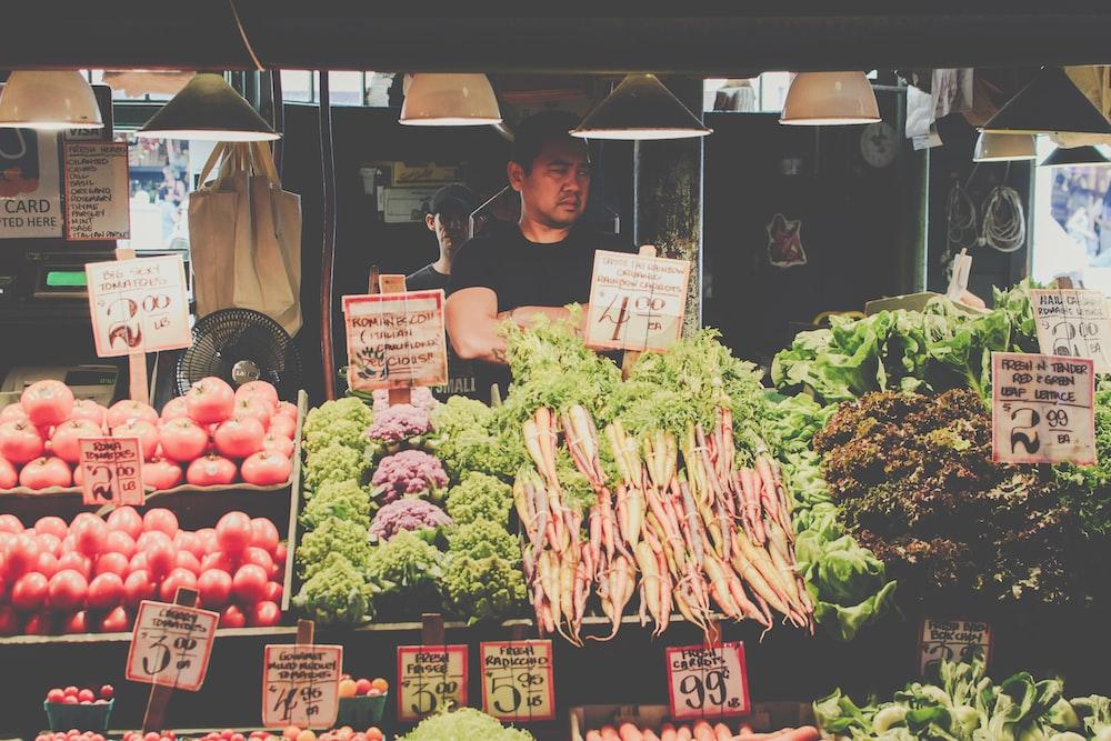 man standing beside vegetables