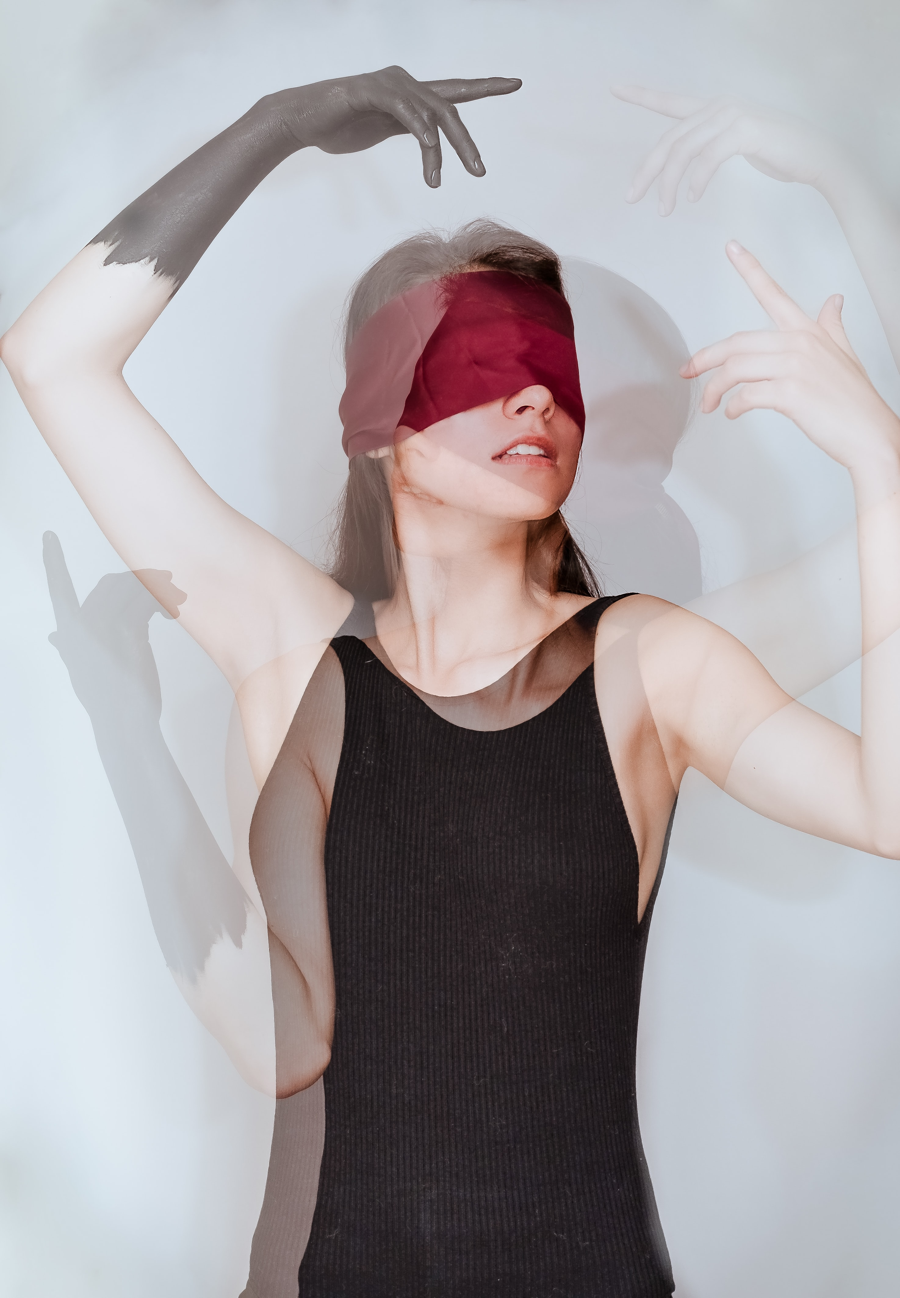 woman with red blindfold wearing black sleeveless top standing beside white wall