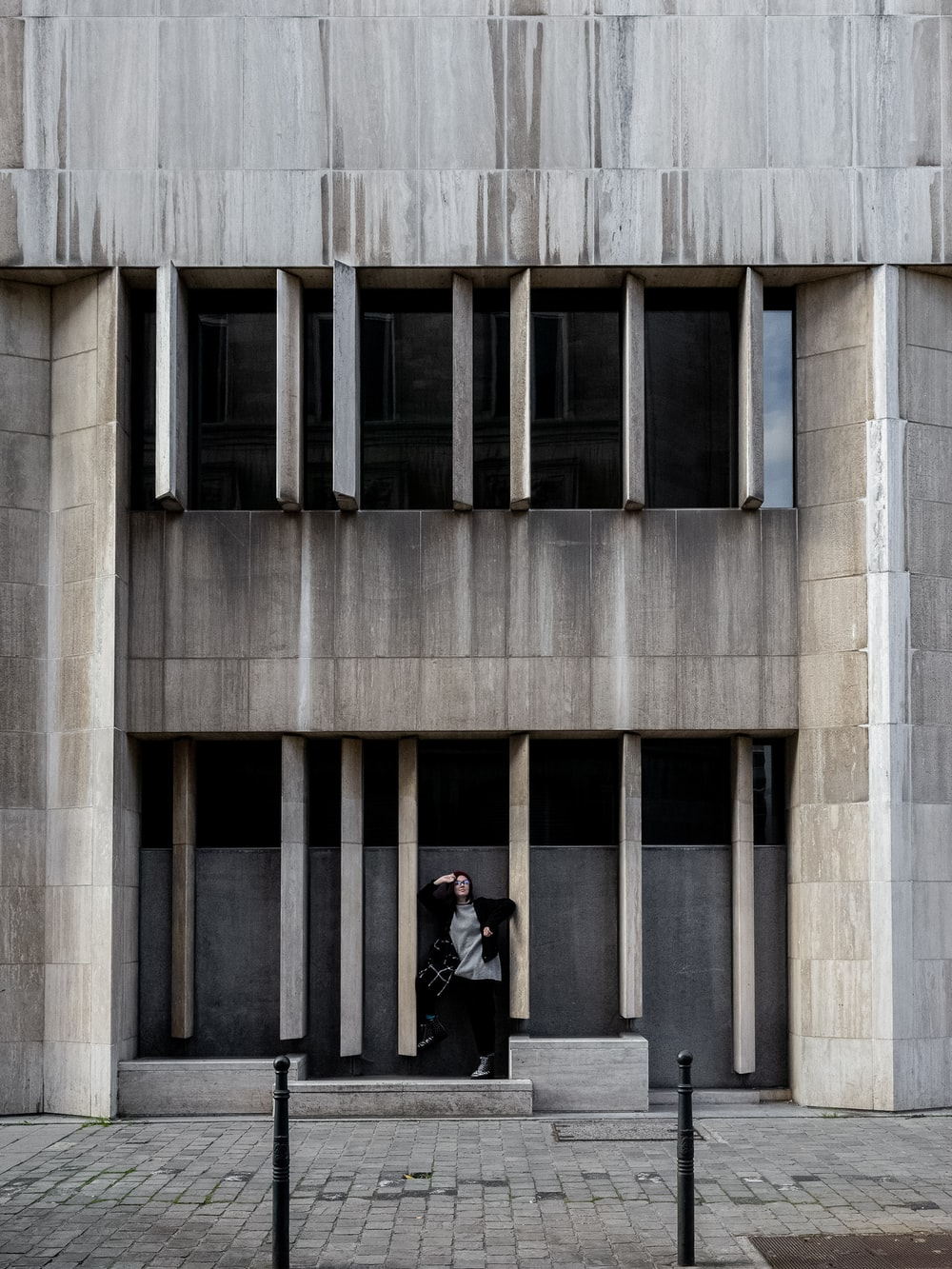 person standing in front of gray concrete building